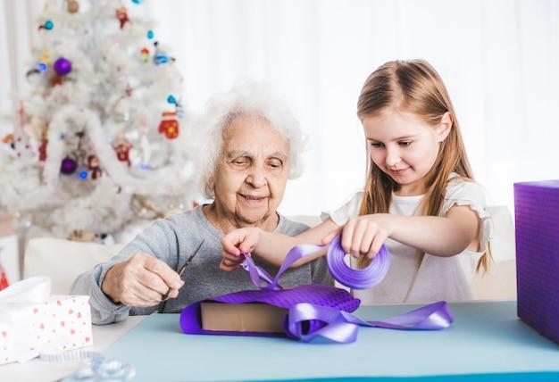 一緒に贈り物を飾る小さな孫娘と一緒に笑顔の祖母