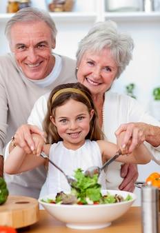 孫娘とサラダを食べる祖父母に笑顔