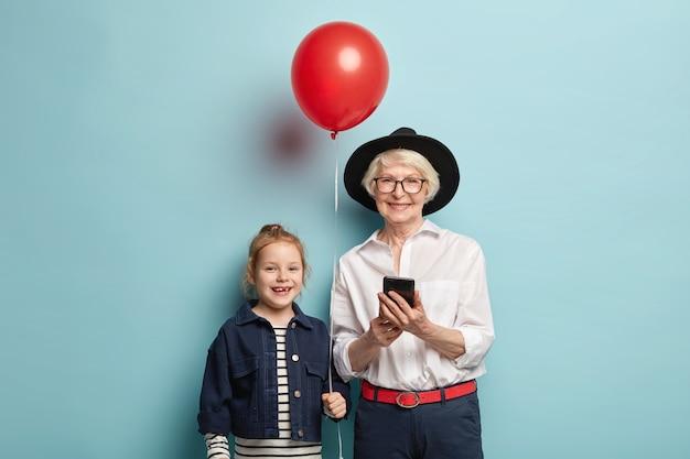 검은 색 세련된 모자, 흰색 우아한 셔츠, 정장 바지를 입은 할머니 미소 짓고, 휴대폰을 들고, 현대 기기를 잘 사용하는 방법을 알고, 빨간 풍선을 들고있는 어린 아이의 생일을 축하합니다.