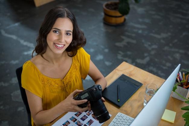 Улыбающийся графический дизайнер с цифровой камерой в творческом офисе