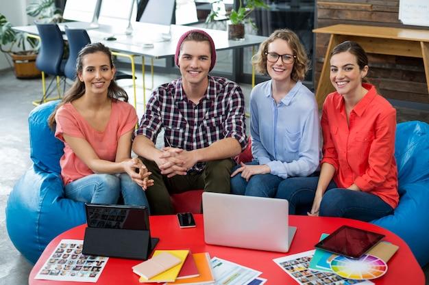 Улыбаясь графических дизайнеров, сидя в офисе с ноутбуком и цифровой планшет на столе