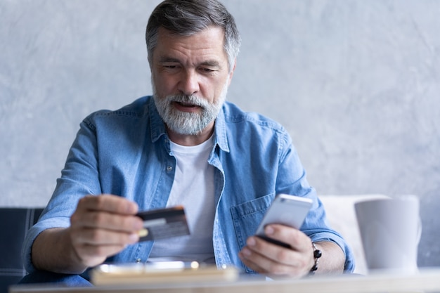 Smiling gray-haired 50s man pay bills online using modern smartphone gadget and credit card. happy mature bank client make internet payment purchase on cellphone from home. technology concept.