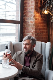 Smiling gray-haired businessman in brown jacket sitting at table and reading label of whisky bottle