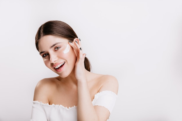 Улыбающаяся зеленоглазая девушка наносит крем на чистое лицо. брюнетка в белом топе позирует на изолированной стене.