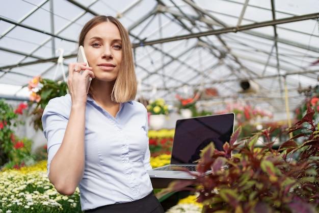 たくさんの花とガラスの屋根を持っている電話で話している彼女の手でラップトップでポーズをとっている温室の所有者の笑顔。