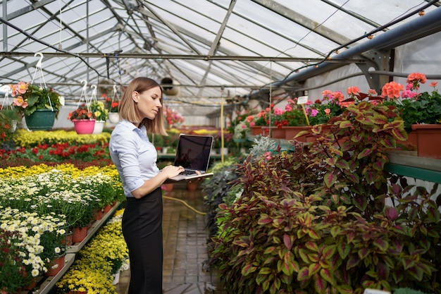 Smiling greenhouse owner posing with a laptop in her hands talking on the phone having many flowers and glass roof.