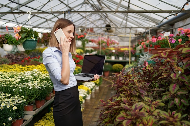Proprietario di serra sorridente in posa con un computer portatile in mano a parlare al telefono con molti fiori e tetto in vetro.