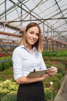 Proprietario di serra sorridente in posa con un blocco note in mano con molti fiori e tetto in vetro