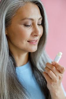 青いtシャツで笑顔の灰色の髪のアジアの女性はピンクの背景にリップクリームを見てください