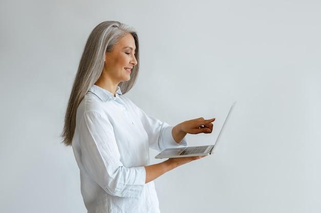 흰 블라우스를 입은 웃고 있는 성숙한 아시아 여성 사업가가 스튜디오 측면의 밝은 배경에 있는 현대적인 노트북 화면을 가리킵니다.
