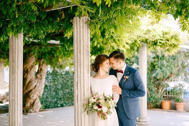 Улыбающийся жених обнимает невесту плечом к колоннам в зеленом саду