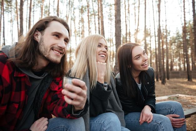 森の中の屋外に座っている友人の笑顔のグループ