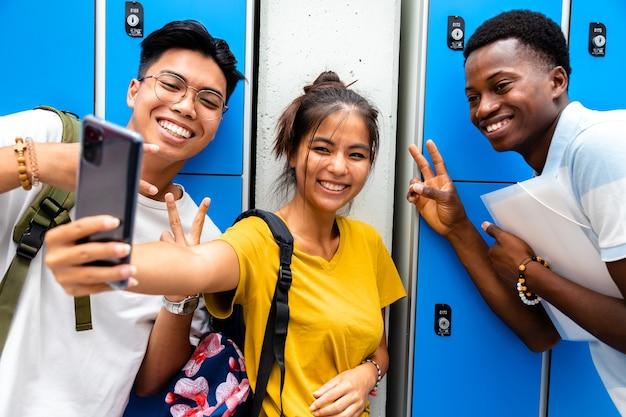高校の廊下で自分撮りをしている多民族の10代の友人の笑顔のグループ。学校のコンセプトに戻ります。友情の概念。