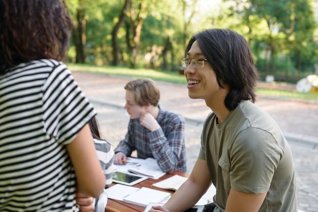 Улыбающаяся группа молодых студентов, сидящих и изучающих