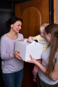 Улыбающиеся гости получают большую коробку с тортом. молодая мама с ребенком встречают гостя с подарком.