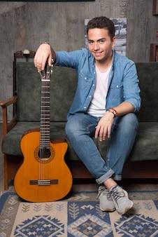 美しいギターを持ってソファに座って笑顔のギタリスト。高品質の写真