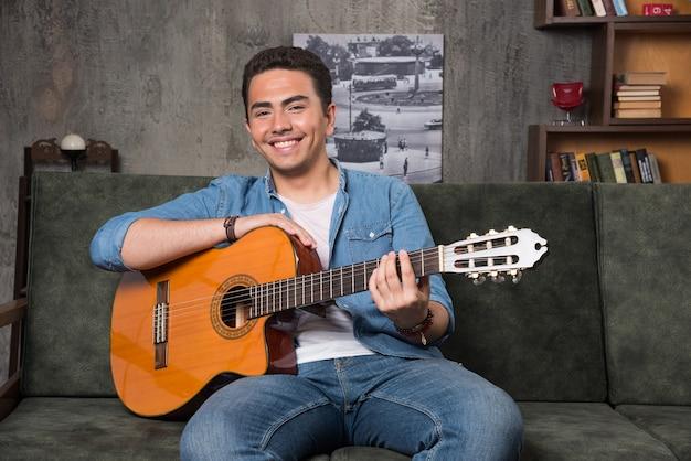 Улыбающийся гитарист держит красивую гитару и сидит на диване. фото высокого качества