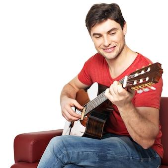 웃는 기타리스트 흰색 배경에 어쿠스틱 guitat isolatade에서 재생됩니다. 잘 생긴 젊은 남자는 긴의 자에 기타와 함께 앉아