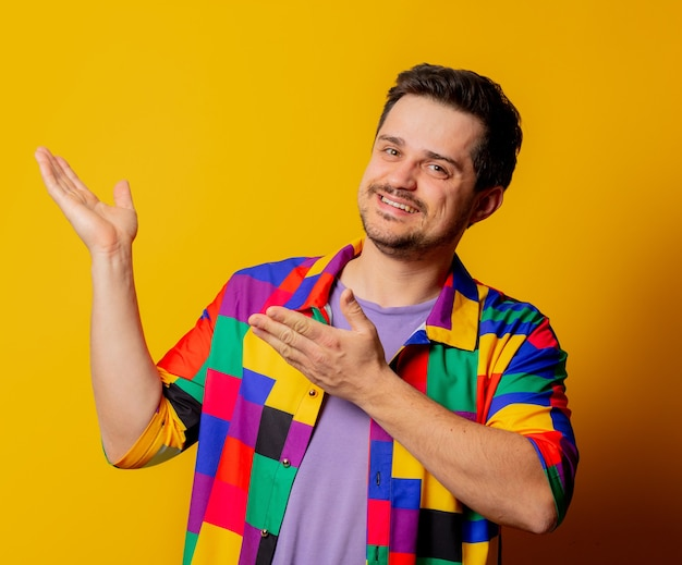 Smiling guy in 90s shirt points with hands