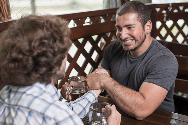 Smiling guy arm wrestling with friend in bar