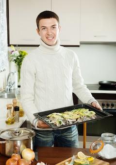 Улыбающийся парень, готовящий форель рыбы в сковороде