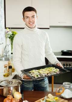 Smiling guy cooking trout fish in roasting pan