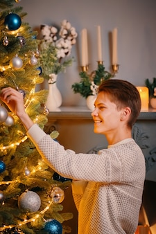 Smiling guy decorating christmas tree. new year's interior with fireplace and candle holder  man in warm knitted sweater hangs holiday decorations.