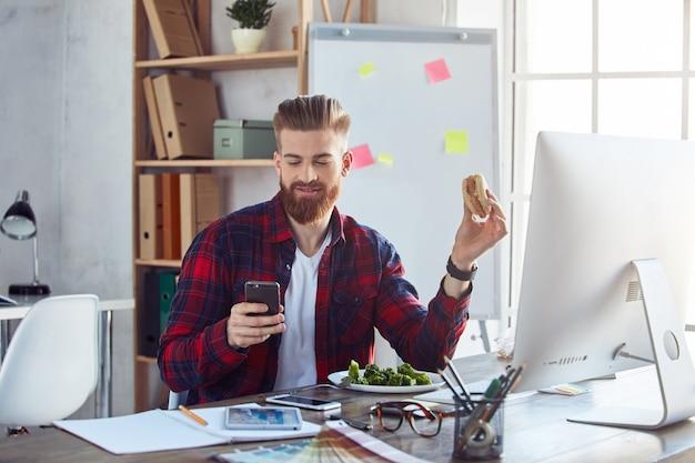 Улыбающийся парень ест гамбургер на рабочем месте во время разговора по телефону
