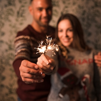 Smiling guy embracing cheerful lady with flaming bengal lights
