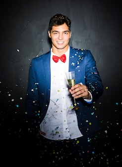 Smiling guy in evening jacket with glass between tossing confetti