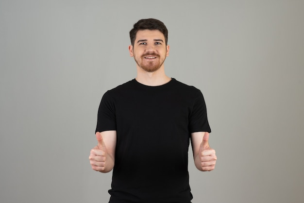 Smiling guy gesturing thumb up on a grey.