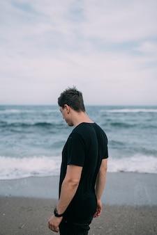 검은 티셔츠에 웃는 남자가 모래 해변에 선다. 여름 날, 흰 구름과 푸른 하늘, 하얀 거품과 파도.