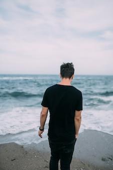黒いtシャツを着た笑顔の男が砂浜の海岸に立っています。