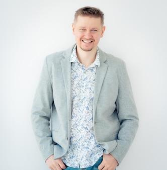 花柄のシャツとジャケットが白い背景で隔離の笑顔の男
