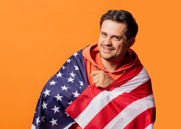 Улыбающийся парень в оранжевой толстовке с флагом сша на оранжевом