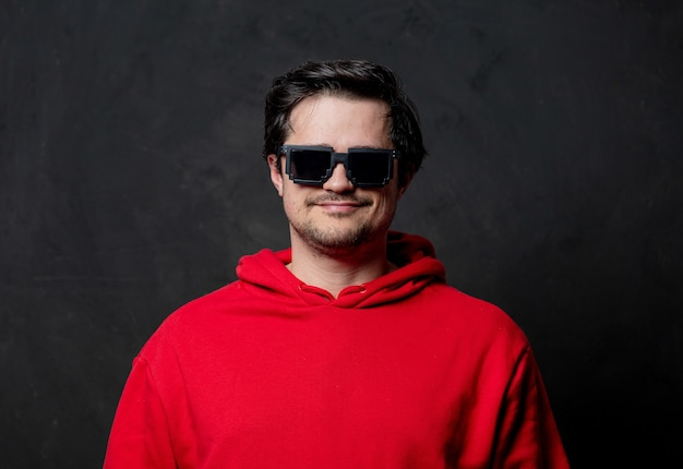 暗い壁に赤いスウェットシャツとサングラスの笑顔の男