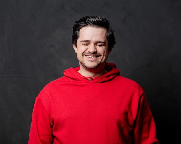暗い壁に赤いスウェットシャツの笑顔の男