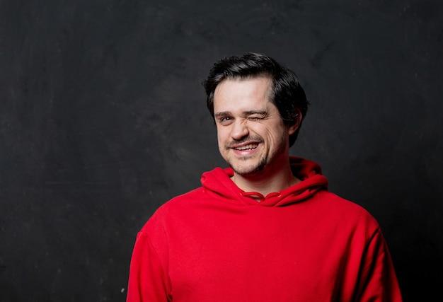 Улыбающийся парень в красной толстовке на темной стене