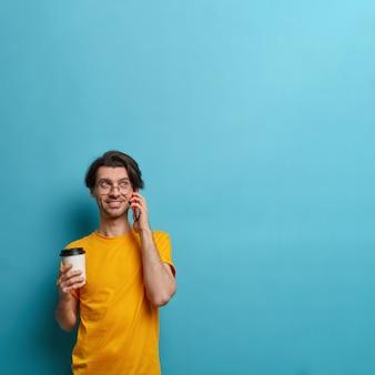 Il ragazzo sorridente tiene il cellulare vicino all'orecchio, impegnato a parlare con un amico, discute di buone notizie, tiene una tazza di caffè da asporto, comunica piacevolmente, posa su sfondo blu, copia spazio per le tue informazioni