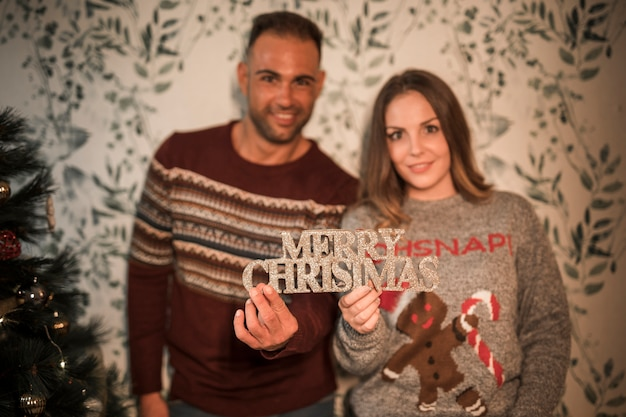 Smiling guy near cheerful lady with merry christmas tablet near decorated fir tree