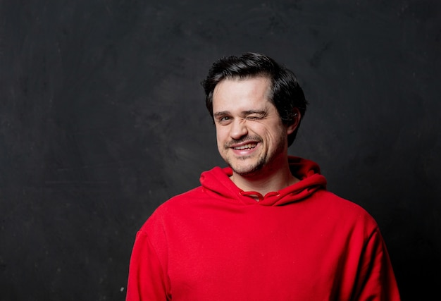 Smiling guy in red sweatshirt on dark wall