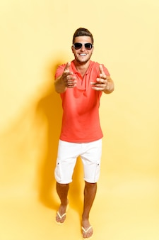 Smiling guy in sunglasses stepping towards camera
