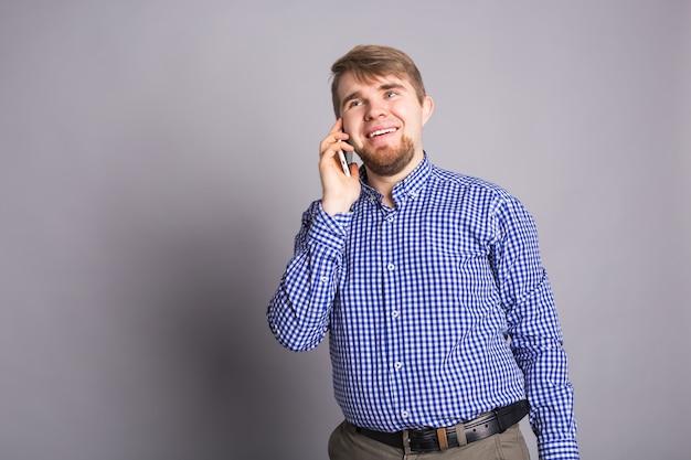 Улыбающийся парень разговаривает по мобильному телефону на серой стене