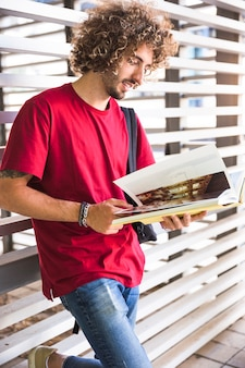 Smiling guy turning pages of textbook