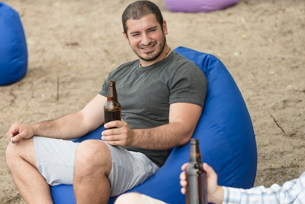 Smiling guy with beer resting near friend