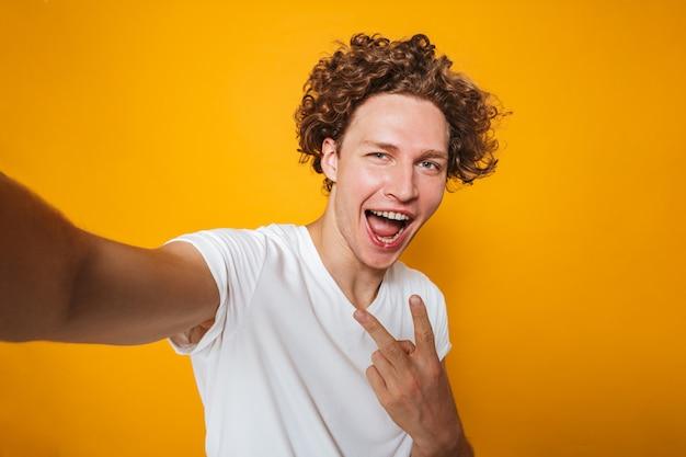 Улыбающийся парень с каштановыми волосами, показывая знак мира на камеру, фотографируя себя с принимая селфи