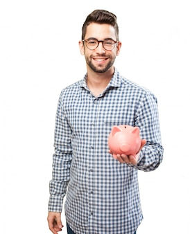 Smiling guy with glasses showing a piggybank
