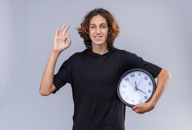 Ragazzo sorridente con capelli lunghi in maglietta nera che tiene un orologio da parete e mostra il gesto okey sul muro bianco