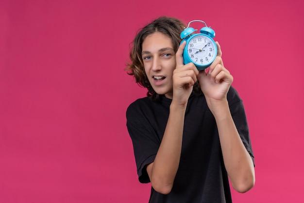 ピンクの壁に目覚まし時計を保持している黒いtシャツの長い髪の笑顔の男