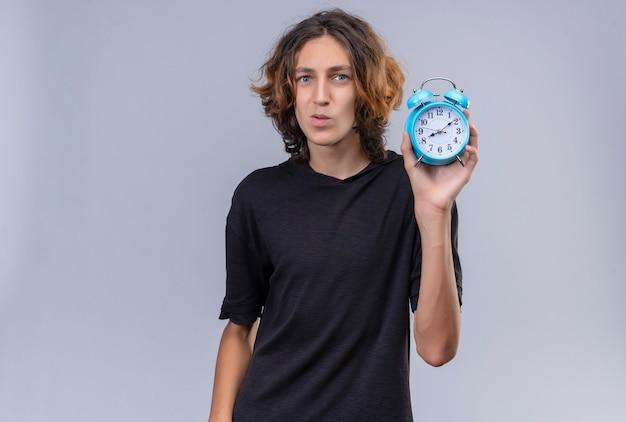 白い壁に目覚まし時計を保持している黒いtシャツの長い髪の笑顔の男